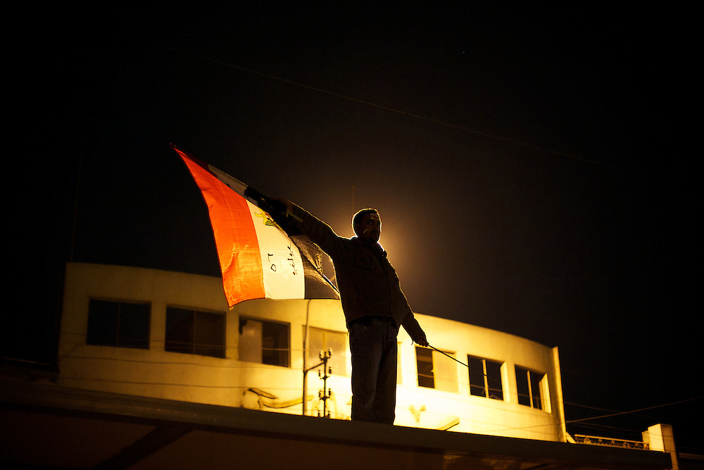 December 11, 2012 - Cairo, Egypt: A protestor waves an egyptian flag on top of a bus stop outside the presidential place in Cairo, where tens of thousands gathered to voice their anger at the planned constitution, which will be put to a referendum next Saturday...The Egyptian army has reportedly called talks between President Mohamed Morsi and the opposition to end violent protests against a draft constitution...Sporadic clashes between supporters and opponents of president Mohamed Morsi, erupted in the past week over his assumption of extraordinary powers and the scheduling of the referendum. (Paulo Nunes dos Santos/Polaris)