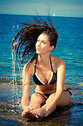 Girl sitting on a rock in a sea splashing water drops with her hair. Looking happy on a sunny day.
