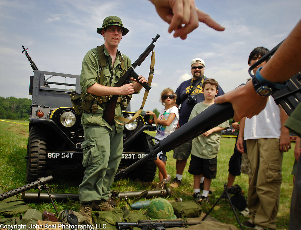 Nathan Jones, a volunteer, stands in front of a gun jeep, displaying and describing a variety of Vietnam War-era weaponry to people during the annual open house at the American Wartime Museum, on Aden Rd. in Nokesville, VA on Saturday, August 21, 2010.  For The News & Messenger (Manassas, VA).