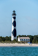 Cape Lookout Lighthouse with lighthouse keepers house and beach on Harkers Island. Riding the ferry to Harkers Island is a popular day trip for visitors to the Crystal Coast, North Carolina, AKA the southern Outer Banks.