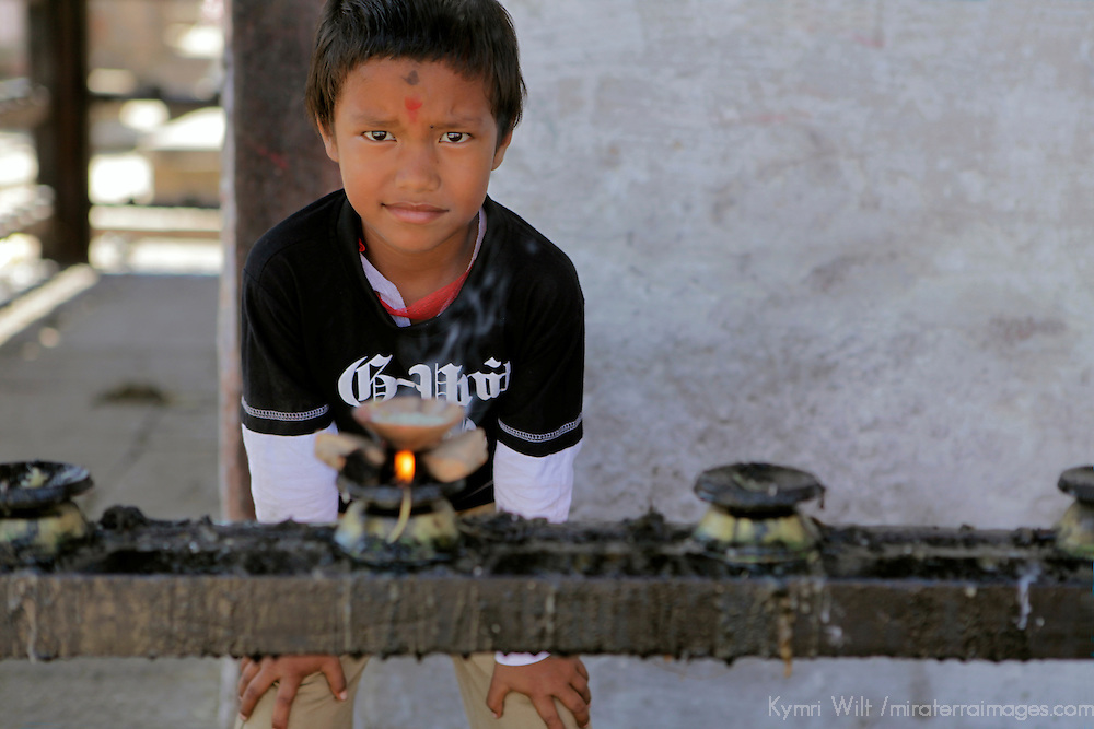 Asia, Nepal, Kathmandu. Young boy lights candle at Hindu Temple.