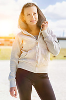 Portrait of young attractive woman smiling while standing and zipping her jacket in park