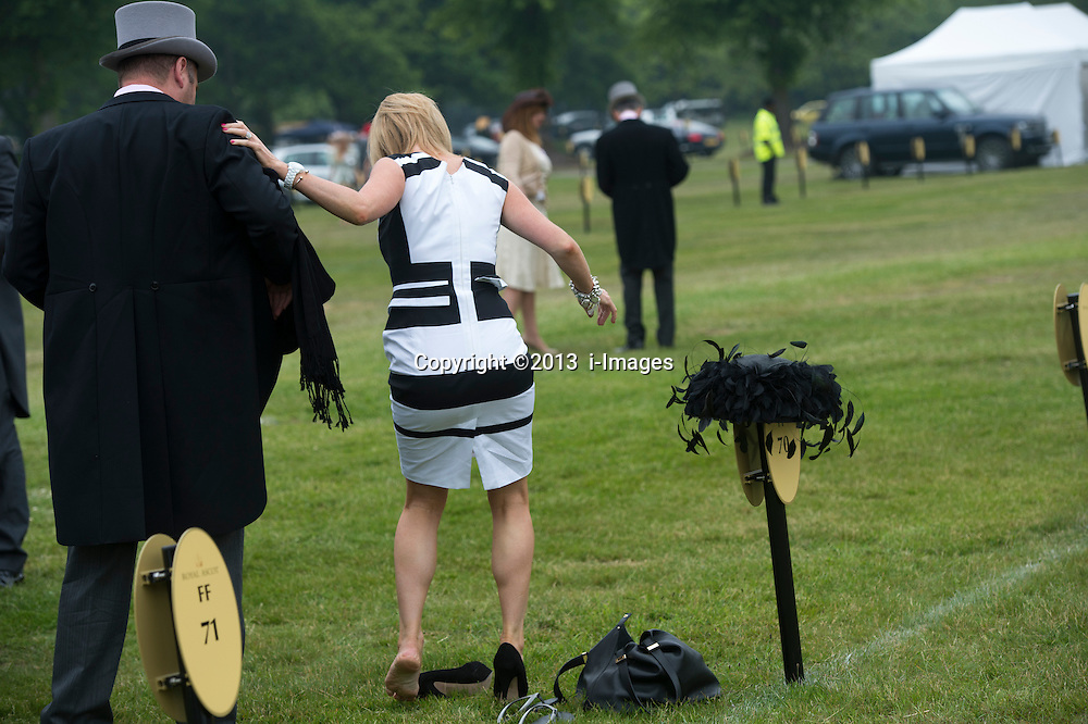 A lady putting her heels on at Royal Ascot 2013,<br /> Ascot, United Kingdom,<br /> Thursday, 20th June 2013<br /> Picture by i-Images