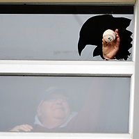 """Erie SeaWolves scoreboard operator Phil """"Bubba"""" Lohr holds up the Altoona Curve foul ball that broke the window in the public-address system booth during the first inning of the Curve's 7-4 baseball win in ten innings at Jerry Uht Park on Monday, May 2, 2016, in Erie, Pa. Photo by Andy Colwell/Erie Times-News"""