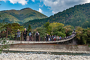 "Suspension bridge. Ogimachi is the largest village and main attraction of the Shirakawa-go region, in Ono District, Gifu Prefecture, Japan. Declared a UNESCO World Heritage Site in 1995, Ogimachi village hosts several dozen well preserved gassho-zukuri farmhouses, some more than 250 years old. Their thick roofs, made without nails, are designed withstand harsh, snowy winters and to protect a large attic space that was formerly used to cultivate silkworms. Many of the farmhouses are now restaurants, museums or minshuku lodging. Some farmhouses from surrounding villages have been relocated to the peaceful Gassho-zukuri Minka-en Outdoor Museum, across the river from the town center. Gassho-zukuri means ""constructed like hands in prayer"", as the farmhouses' steep thatched roofs resemble the hands of Buddhist monks pressed together in prayer."