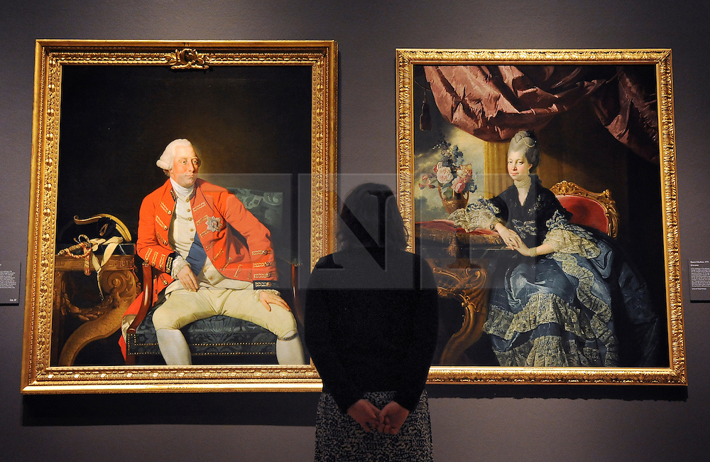 © Licensed to London News Pictures. 06/03/2012. London, UK. A woman looks at central portraits from the Royal Collection of George III and Queen Charlotte painted in 1771. Photo call for Johan Zoffany's portraits of George III and Queen Charlotte ahead of Johan Zoffany RA: Society Observed. The exhibition runs at the Royal Academy of Arts from March 10 to June 10 in Piccadilly, London. Photo credit : Photographer Stephen SImpson/LNP
