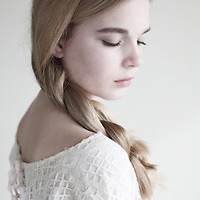 Female youth close up with eyes closed looking to side with plaited blonde hair