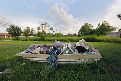 20 August 2015. New Orleans, Louisiana. <br /> Hurricane Katrina revisited. <br /> A decade later and recovery remains largely elusive for the area hardest hit by Katrina. A boat filled with debris remains on an abandoned lot flooded in the storm.<br /> Photo credit©; Charlie Varley/varleypix.com.