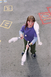 Young girl juggling clubs,