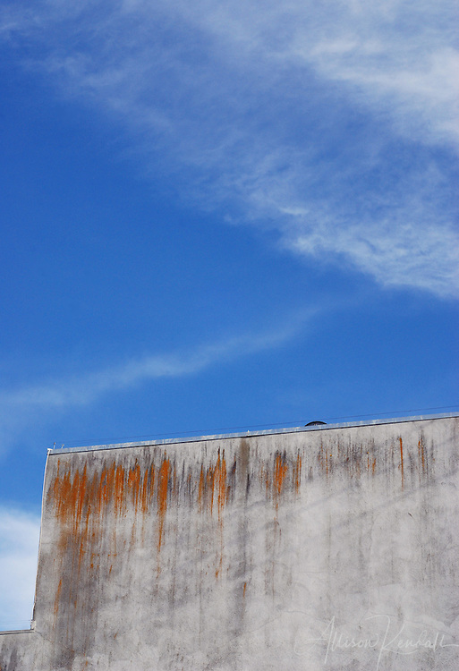 Blue skies rise above a rusted, weathered rooftop.