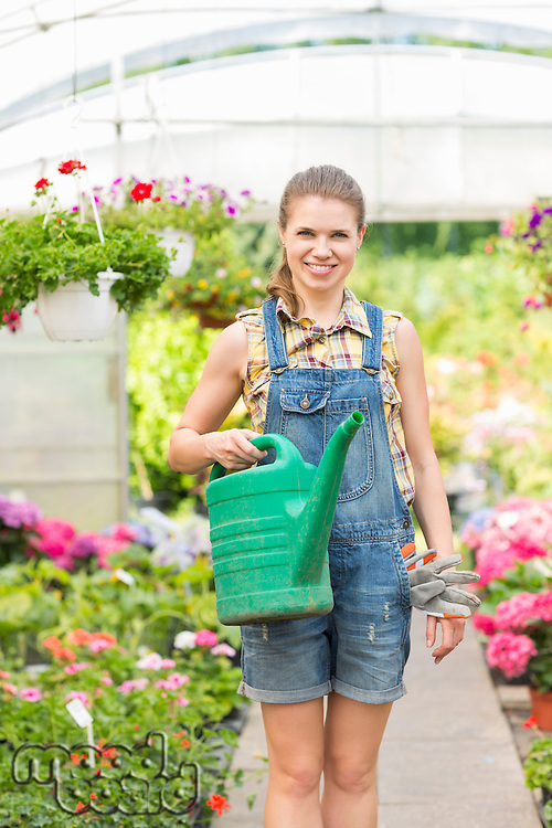 Portrait of happy female gardener holding watering can in greenhouse