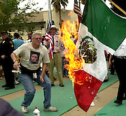 Counter protester, Roy Warden, burns the flag of Mexico as demonstrators protest at a march in Tucson, Arizona, regarding proposed immigration legislation.