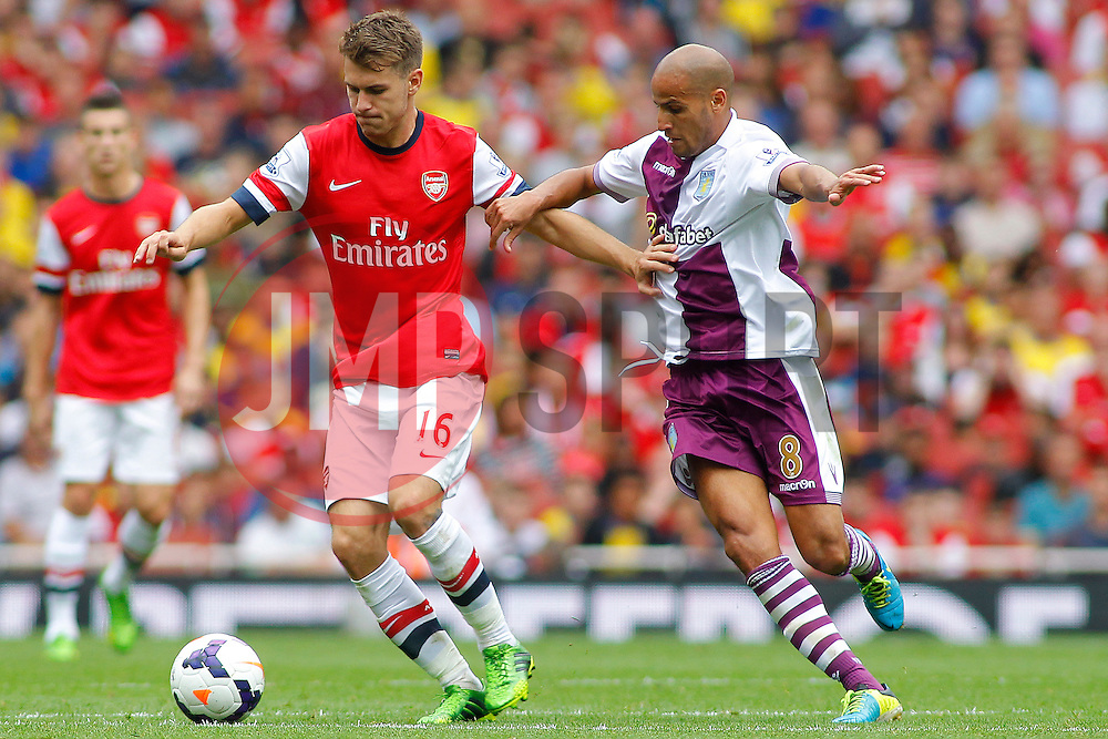 Arsenal's Aaron Ramsey and \Aston Villa's Karim El Ahmadi compete for the ball  - Photo mandatory by-line: Mitch Gunn/JMP - Tel: Mobile: 07966 386802 17/08/2013 - SPORT - FOOTBALL - Emirates Stadium - London -  Arsenal V Aston Villa - Barclays Premier League
