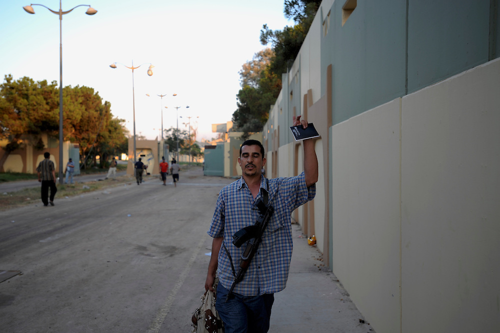 A rebel fighter gestures a victory signal during the take of Muammar Gaddafi's Bab Al Azizia compound in Tripoli.
