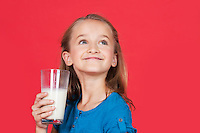 Young girl holding glass of milk while looking up on red background