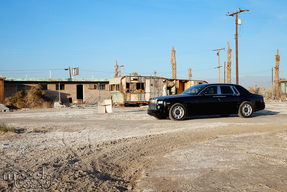 Rolls Royce parked in front of abandoned houses