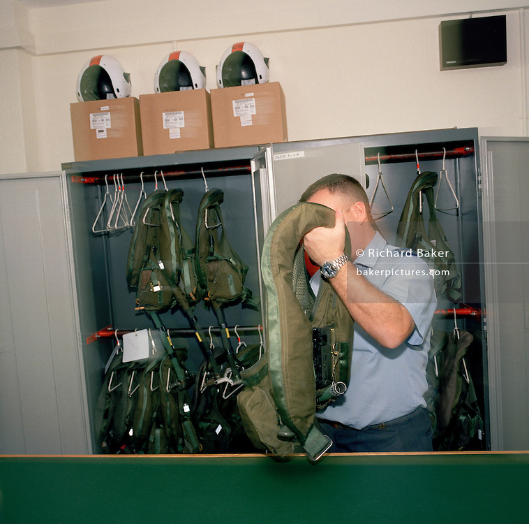 Equipment supplier checks flying pilots' survival vests of 'Red Arrows', Britain's Royal Air Force aerobatic team.