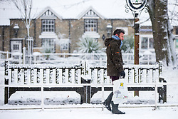 © Licensed to London News Pictures. 30/11/2017. Thornton Le-Dale UK. A man walks past a snow covered bench this morning after a night of heavy snow this in the village of Thornton Le-Dale in North Yorkshire.Photo credit: Andrew McCaren/LNP