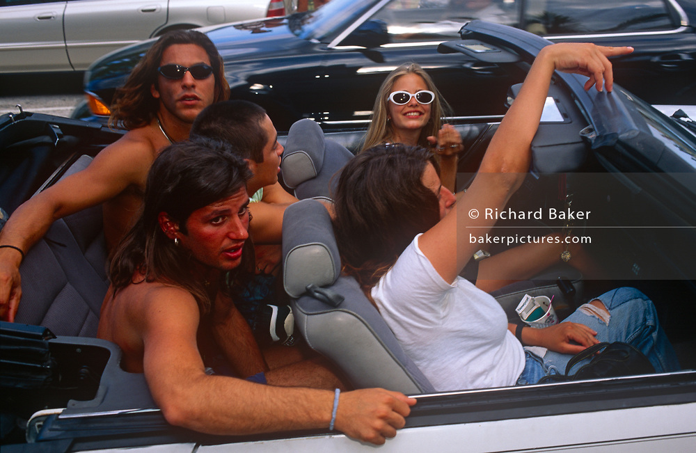 Young people enjoy a drive in an open-top car along Ocean Drive, on 15th May 1996, in Miami Beach, Florida, USA.