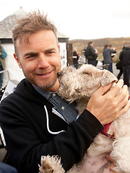 © Licensed to London News Pictures. 18/04/2013. Lands End, UK. Garry Barlow poses for photos with a dog ahead of their Lands End to John O'Groats drive in a pink Rolls Royce. The aim is to raise 1 Million pounds for Breast Cancer Care. Photo credit : Ashley Hugo/LNP