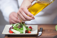 Mid- adult chef pours olive oil over side salad