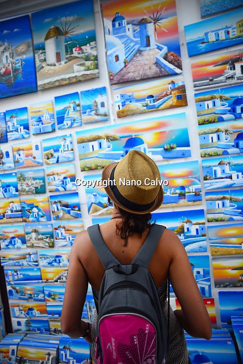 Young woman looking at paintings in street store, Mykonos, Greece