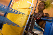 A woman uses traditional looms to weave textile at the Village Artisanal de Ouagadougou, a cooperative that employs dozens of artisans who work in different mediums, in Ouagadougou, Burkina Faso, on Monday November 3, 2008.
