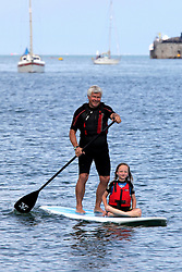 © Licensed to London News Pictures. 23/05/2015. Bembridge, Isle of Wight, UK. Eva Mitchell, aged seven from Cowes, with her grandfather on a paddleboard enjoying the war, and sunny weather at the Duver beach in St. Helens, Isle of Wight today, Bank Holiday Saturday 23rd May 2015 . Photo credit : Rob Arnold/LNP