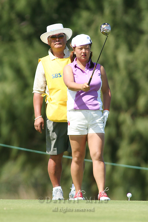 February 16, 2006 - Kahuku, HI - Christina Kim lines up her tee shot while her father/caddy look on during Round 1 of the LPGA SBS Open at Turtle Bay Resort...Photo: Darrell Miho