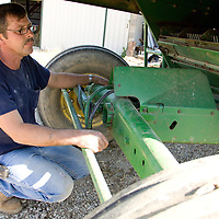 Tim Fox fixes the combine before harvesting corn. His mechanic abilities come in handy in this line of work.