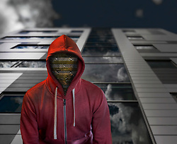 Computer board in face of hooded figure. Cybercrime. Low angle, large modern building with glass exterior wall. Clouds reflecting on windows.