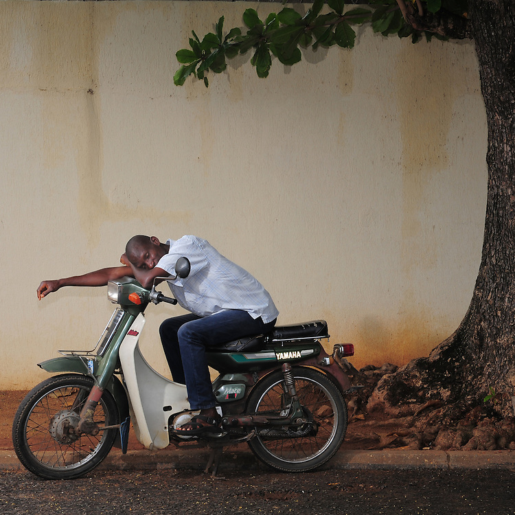 12-05-29   - LOME, TOGO -    Zemidjan ('take me quickly' in  Fon) driver Justin Agbendjia demonstrates how he sleeps on his motorcycle in Lomé, Togo on May 29. Underpaid, rarely thanked and working all hours to make a meagre living, they find very few moments of calm and quiet in their lives. And so, the moto-taxi men have perfected various ways of calmly sleeping on their motorbike as they wait for  their next customer. And so, on the move amidst the chaos and bustle of daily life, they relax and sleep.  Photo by Daniel Hayduk