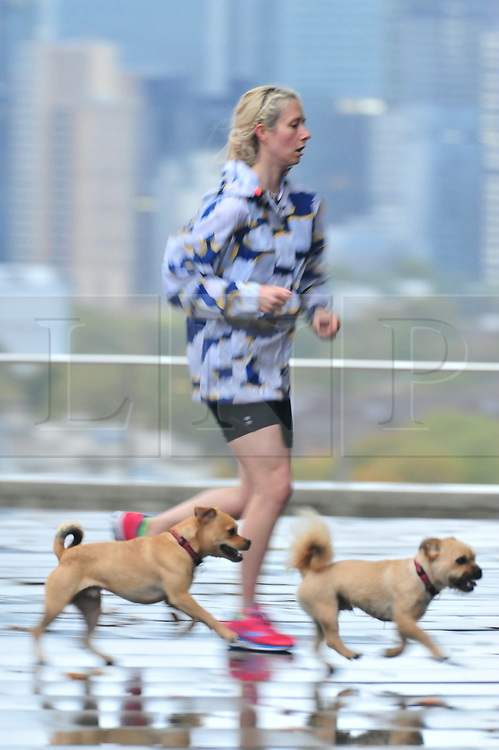 © Licensed to London News Pictures. 14/10/2018<br /> GREENWICH, UK.<br /> Lady running with her dogs.<br /> Wet weather morning in Greenwich Park, Greenwich as Storm Callum hits the UK.<br /> Photo credit: Grant Falvey/LNP