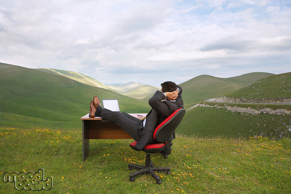 Businessman relaxing with feet on desk in mountain field side view