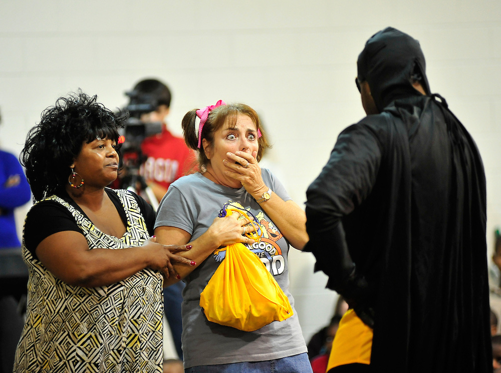 Eala Shrieves, left, and Karen Flynn react as they get a surprise lesson on bus safety from Captain Safety played by Runako Hull as a group of Athens-Clarke school bus drivers perform a skit about bus safety at Alps Road Elementary School on Wednesday, Nov. 3, 2010 in Athens, Ga. .