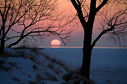Setting sun dipping in the icy waters of Lake Michigan in winter