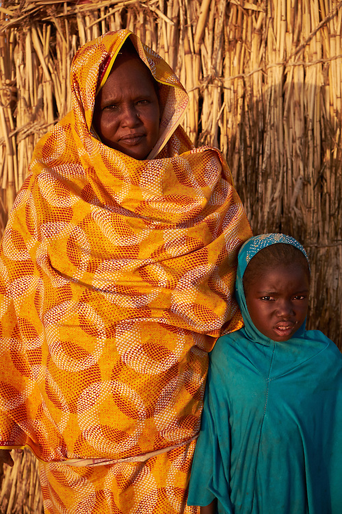 Djarou Ali, 45 and her daughter Hawa Babacar at a camp of displaced people in the neighbourhood of Chateau, Diffa, Niger on February 12, 2016. The camp is mixed between displaced people from Niger, Nigeria and Chad. They have fled attacks by the militant group Boko Haram on their villages and it's ongoing conflicts with the armies of each country. Caritas undertook a distribution of mosquito nets, cooking pots, sleeping covers, hygiene kits, clothes and cash transfers to the displaced. 228 households received support from Caritas among an estimated 1500 households in the  vicinity of Chateau. There is still great need. There is no school system in place for the children and the housing is not adequate for many as more people arrive each day escaping hostilities. <br /> <br /> 'My husband disappeared and I expect he is dead because I have not seen him in over a year. I have support from other people in the community, those displaced and also the Nigeriens who are compassionate enough to give me something to eat or some money to support my family.'