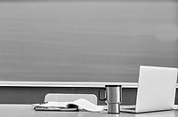 Black and white photo of laptop on professor desk with tumbler and book against black board in classroom