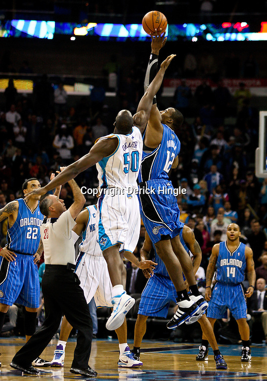 Feb 26, 2010; New Orleans, LA, USA; Orlando Magic center Dwight Howard (12) and New Orleans Hornets center Emeka Okafor (50) jump for the opening tip of the first quarter at the New Orleans Arena. Mandatory Credit: Derick E. Hingle-US PRESSWIRE