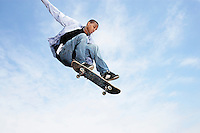 Man jumping on skateboard in air low angle view