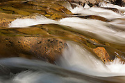 The rugged granite surface that forms the bed of the Tenaya River is turned golden by the late evening sun in Yosemite National Park, California.