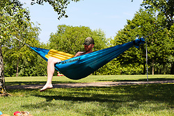 © Licensed to London News Pictures. 22/06/2020. London, UK. A man in a hammock in Finsbury Park, north London on a warm and sunny day in the capital. According to the Met Office, the temperatures are forecast to reach between 31 and 33 degrees celsius in the south-east of England later this week. Photo credit: Dinendra Haria/LNP