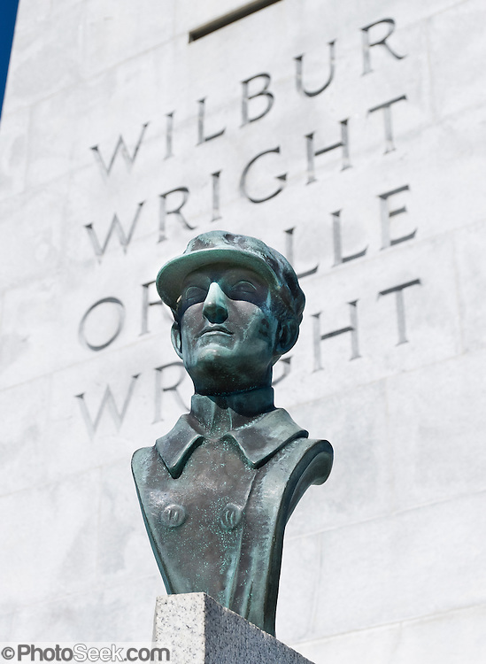 """Wilbur Wright bronze bust.  Wright Brothers National Memorial (or Kill Devil Hill Monument from 1927 to 1933), located in Kill Devil Hills, in Dare County, North Carolina, USA, commemorates the first successful, sustained, powered flights in a heavier-than-air machine. The memorial tower, built in 1932, was designed by Rodgers and Poor, a New York architectural firm. From 1900 to 1903, Orville Wright (born August 19, 1871 - died January 30, 1948) and Wilbur Wright (April 16, 1867 - May 30, 1912) came here from Dayton, Ohio, attracted to the area's steady winds and privacy. The town of Kitty Hawk (established in the early 1700s as Chickahawk) was made famous on December 17, 1903, when the Wright brothers made the first controlled, powered airplane flights six kilometers (4 miles) away near the sand dunes known as Jockey's Ridge.  In the two years afterward, the brothers developed their flying machine into the first practical fixed-wing aircraft. Although not the first to build and fly experimental aircraft, the Wright brothers were the first to invent aircraft controls that made fixed wing flight possible. The brothers' fundamental breakthrough was their invention of """"three axis-control"""", which enabled the pilot to steer the aircraft effectively and to maintain its equilibrium, a method which became standard on modern fixed wing aircraft."""