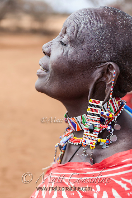 Masai woman in traditional beadwork jewellery singing a welcome in Kenya, Africa (photo by Travel Photographer Matt Considine)
