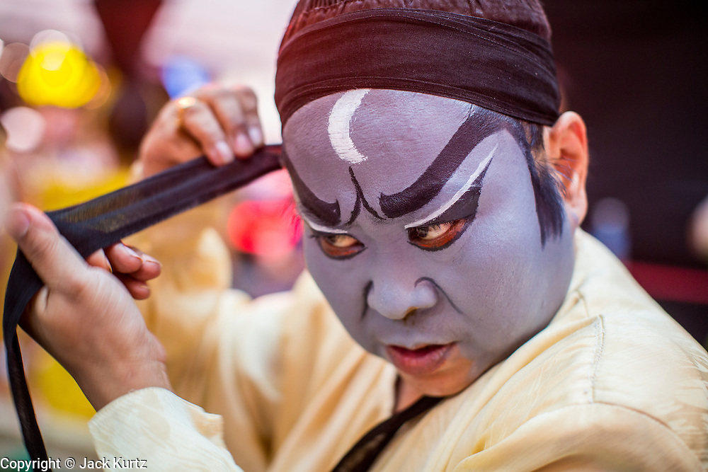 08 FEBRUARY 2013 - BANGKOK, THAILAND:  The lead character of the Judge (or Magistrate) puts the finishing touches on his costume before performing a Chinese opera for Chinese New Year at Seacon Square in Bangkok. Chinese opera is popular in Thailand and is usually performed in the Teochew language. The weeks surrounding Chinese New Year are important for retailers in Thailand and many malls put on special promotions and events honoring Chinese culture, like Lion Dances or Chinese Opera. Thailand has a large Thai-Chinese population. Millions of Chinese emigrated to Thailand (then Siam) in the 18th and 19th centuries and brought their cultural practices with them.   PHOTO BY JACK KURTZ