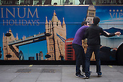 A parked tour coach for Platinum Holidays features famous London landmarks as two boys playfully fight over a drink.