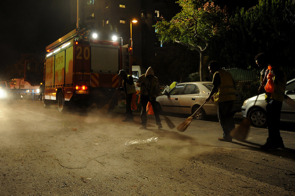 Rishon Letzion, Israel - November 20, 2012: People sweep the street near a building in Rishon Letzion, located near Tel Aviv, that was directly hit by a rocket, fired from Gaza Strip, causing the light injury of two cevilians, at the Seventh day of Operation Pillar of Defense. Photo by Gili Yaari  - Israel Photojournalist