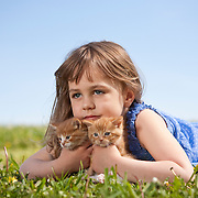 Contemplative girl 4-6 years in dress lying on grass holding two kittens