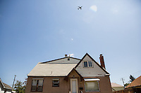 A commerical airplane flies over the Revive House Friday, July 24, 2015 in northern portion of Spokane, Wash.
