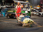 29 FEBRUARY 2016 - BANGKOK, THAILAND: A woman crosses the street in front of the Bangkok flower market with a boy in her family. Many of the sidewalk vendors around Pak Khlong Talat, the Bangkok flower market, closed their stalls Monday. As a part of the military government sponsored initiative to clean up Bangkok, city officials announced new rules for the sidewalk vendors that shortened their hours and changed the regulations they worked under. Some vendors said the new rules were confusing and too limiting and most vendors chose to close Monday rather than risk fines and penalties. Many hope to reopen when the situation is clarified.    PHOTO BY JACK KURTZ